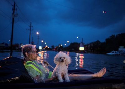 A rescue helicopter hovers in the background as an elderly woman and her poodle use an air mattress to float above flood waters from Tropical Storm Harvey while waiting to be rescued from Scarsdale Boulevard in Houston